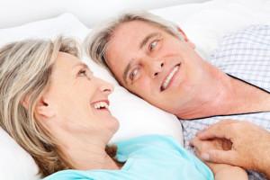 Zwei lachende Senioren kuscheln im Bett im Schlafzimmer